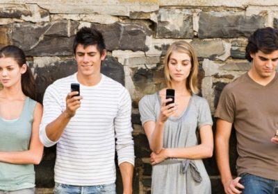 Personas leyendo el chat de su teléfono, probablemente Whatsapp.